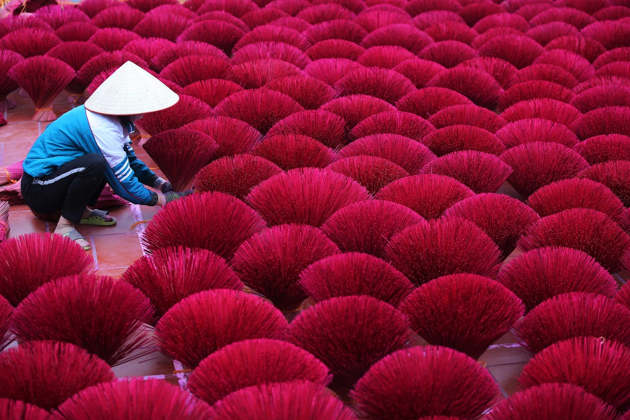 2019-01-17: A woman arranges incense sticks to dry inside a temple's yard, in Quang Phu Cau village on the outskirts of Hanoi, Vietnam on  Jan. 17, 2019. The village which is believed to have started making incense more than 100 years ago, is now busy perparing for the upcoming Lunar New Year