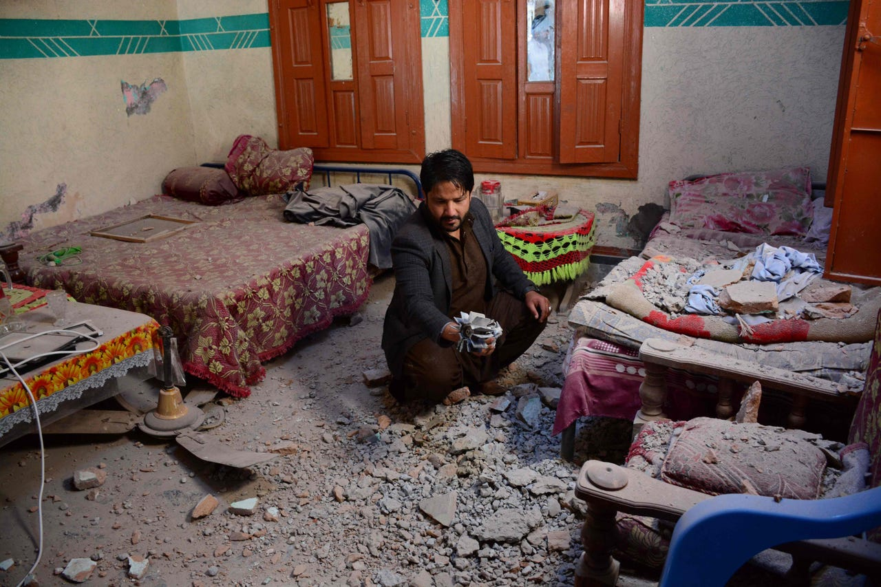 2019-03-06: Pakistani Kashmiri resident Abdul Shakoor holds a piece of mortar shell fired by cross border Indian troops that hit and damaged his house in Dhanna village near the Line of Control (LoC) in Pakistan-administered Kashmir on March 6, 2019.