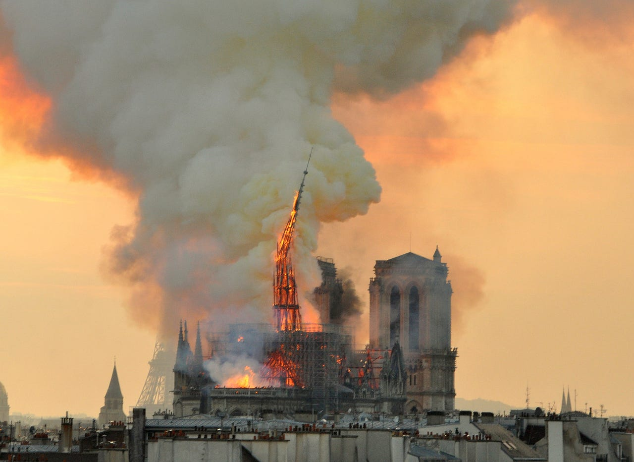 2019-04-15: Flames and smoke rise from the blaze as the spire starts to topple on Notre Dame cathedral in Paris, April 15, 2019. An inferno that raged through Notre Dame Cathedral for more than 12 hours destroyed its spire and its roof but spared its twin medieval bell towers, and a frantic rescue effort saved the monument's 'most precious treasures,' including the Crown of Thorns purportedly worn by Jesus, officials said.