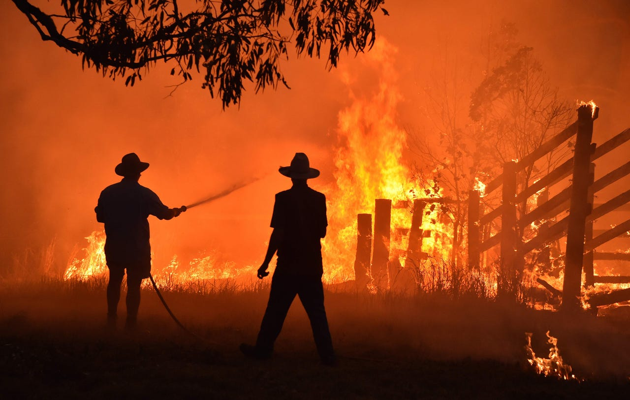2019-11-12: Residents defend a property from a bushfire at Hillsville near Taree, around 215 miles north of Sydney on Nov. 12, 2019. A state of emergency was declared on Nov. 11 and residents in the Sydney area were warned of 'catastrophic' fire danger as Australia prepared for a fresh wave of deadly bushfires that have ravaged the drought-stricken east of the country.