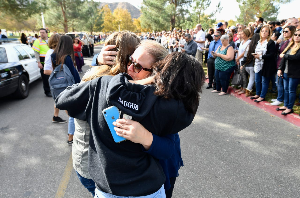 2019-11-14: A parent is reunited with her children after two students were killed and others were injured during a shooting at Saugus High School in Santa Clarita, California on Nov. 14, 2019.