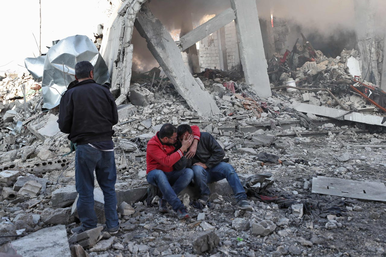 2019-12-07: A Syrian man comforts another on the rubble of a building after a reported Russian airstrike on a popular market in the village of Balyun in Syria's northwestern Idlib province, on Dec. 7, 2019. Syrian regime and Russian air strikes killed 19 civilians on Dec. 7, eight of them children, in Idlib, the country's last major opposition bastion, a war monitor said.